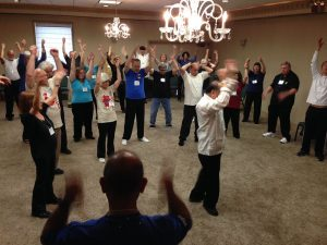 A group of people engaging in a TaiChi coaching conducted in indoor setting